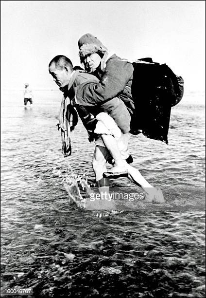 A Korean civilian carries his father on his back as they cross the Han river 30 January 1951 Despite the counter offensive launched by UN troops to...