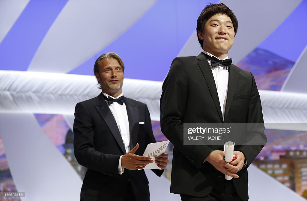 Korean director Moon Byung-gon celebrates on stage on May 26, 2013 in front of Danish actor Mads Mikkelsen, after he was awarded with the Palme d'Or for Best Short Film for 'Safe' during the closing ceremony of the 66th edition of the Cannes Film Festival in Cannes.