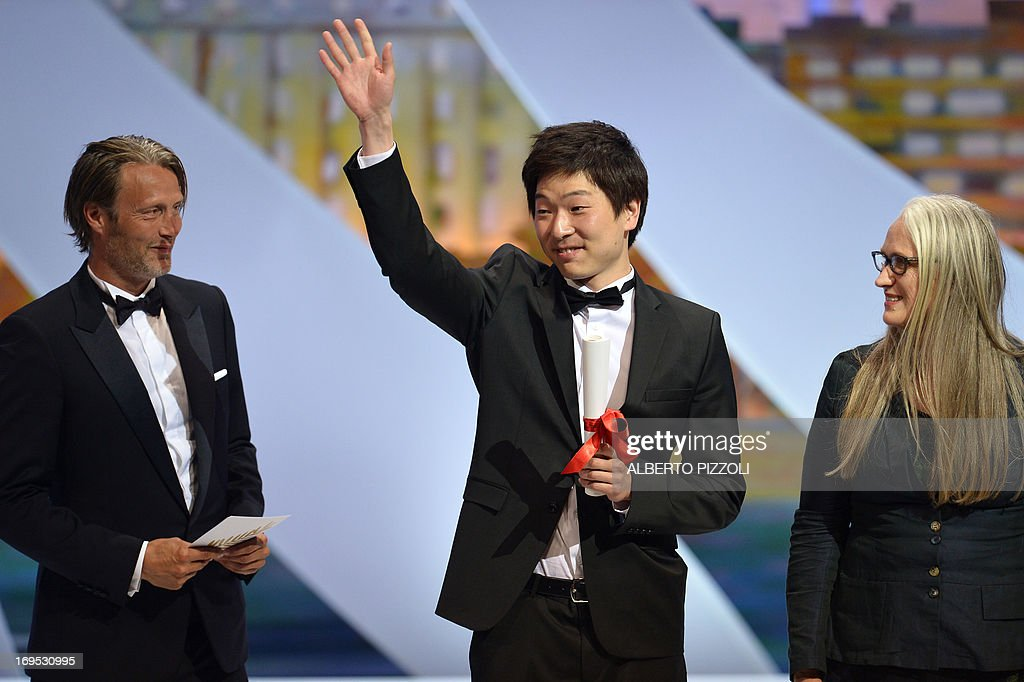 Korean director Moon Byung-gon celebrates on stage on May 26, 2013 with Danish actor Mads Mikkelsen (L) and New Zealand director and President of the Cinefondation and Short Films Jury Jane Campion, after he was awarded with the Palme d'Or for Best Short Film for 'Safe' during the closing ceremony of the 66th edition of the Cannes Film Festival in Cannes. AFP PHOTO / ALBERTO PIZZOLI