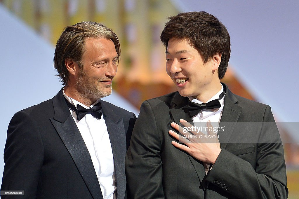 Korean director Moon Byung-gon (R) looks on May 26, 2013 at Danish actor Mads Mikkelsen after he was awarded with the Palme d'Or for Best Short Film for 'Safe' during the closing ceremony of the 66th edition of the Cannes Film Festival in Cannes.