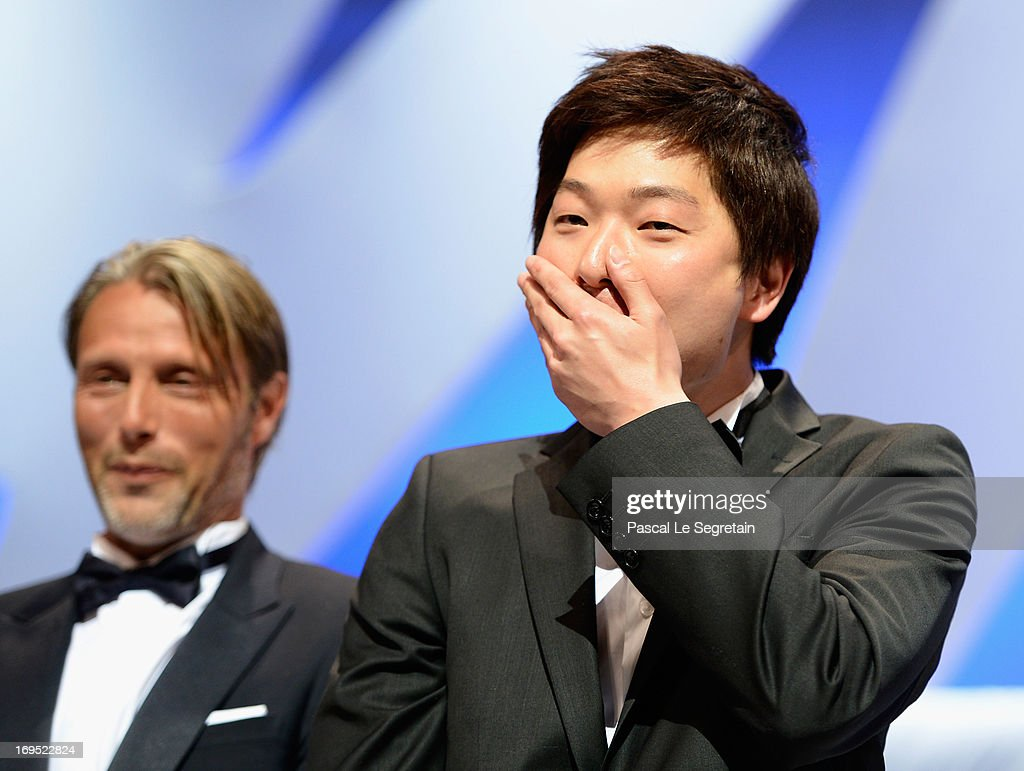Korean director Moon Byung-gon poses on stage with actor Mads Mikkelsen after winning the Palme d'Or for Short Film for the film 'Safe' at the Inside Closing Ceremony during the 66th Annual Cannes Film Festival at the Palais des Festivals on May 26, 2013 in Cannes, France.