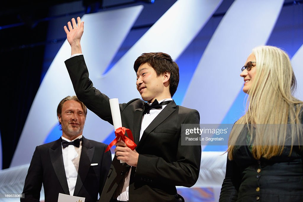 Korean director Moon Byung-gon (C) poses on stage with actor Mads Mikkelsen (L) and director Jane Campion (R) after winning the Palme d'Or for Short Film for the film 'Safe' at the Inside Closing Ceremony during the 66th Annual Cannes Film Festival at the Palais des Festivals on May 26, 2013 in Cannes, France.