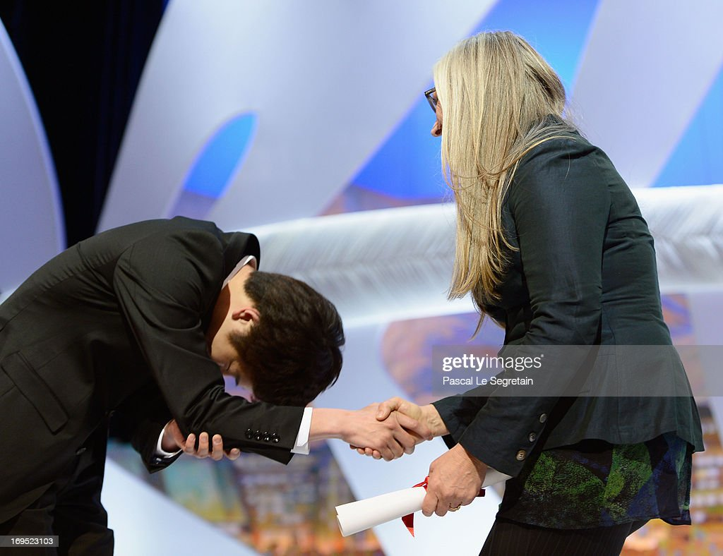 Korean director Moon Byung-gon (C) receives on stage from director Jane Campion (R) the Palme d'Or for Short Film for the film 'Safe' after winning at the Inside Closing Ceremony during the 66th Annual Cannes Film Festival at the Palais des Festivals on May 26, 2013 in Cannes, France.