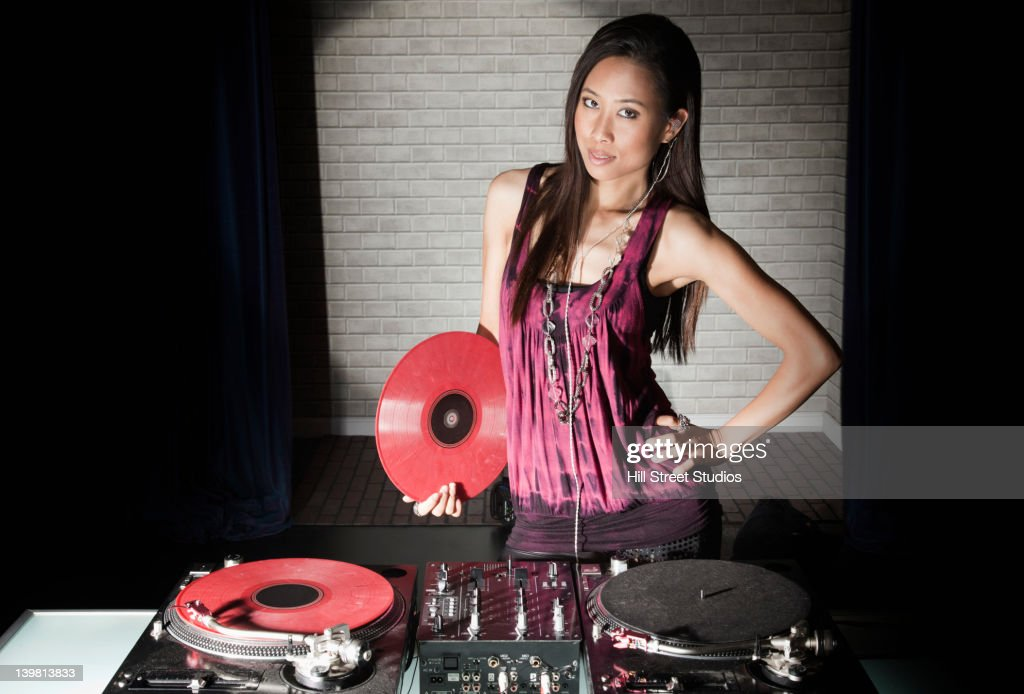Korean DJ standing with turntables in nightclub : Stock Photo