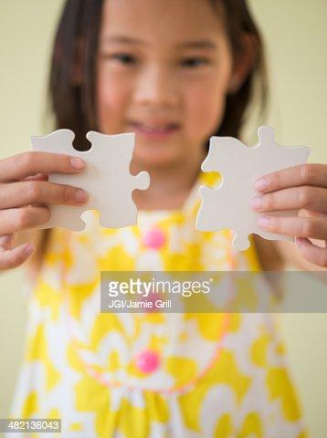 Korean girl connecting jigsaw pieces