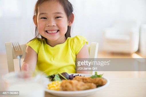 Happy asian girl stock photos and pictures getty images for Japanese eating table