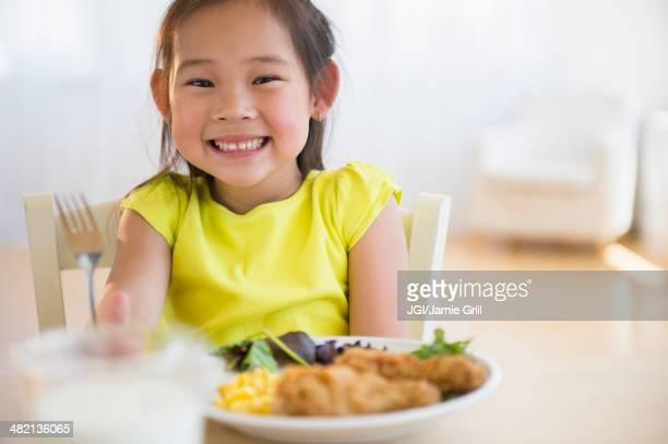 Korean girl eating dinner at table