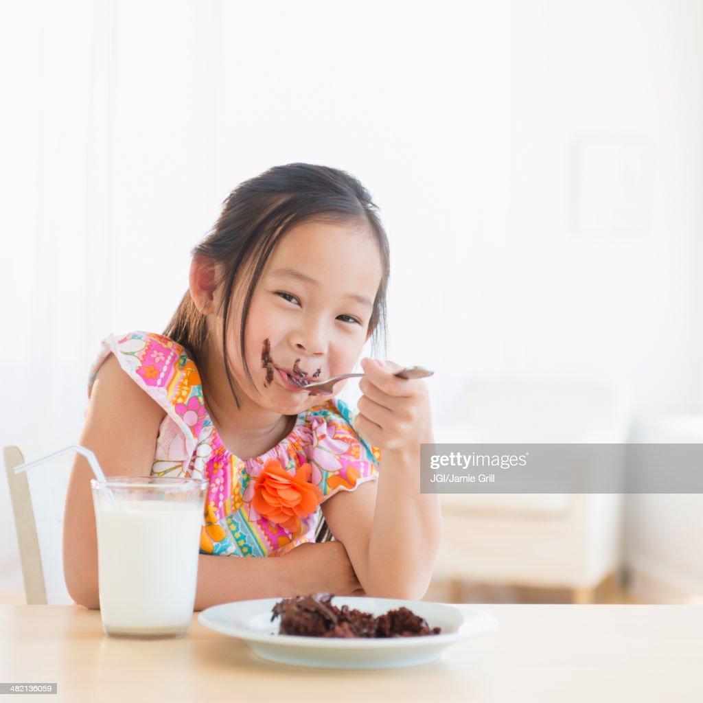 Korean girl eating slice of chocolate cake : Stock Photo