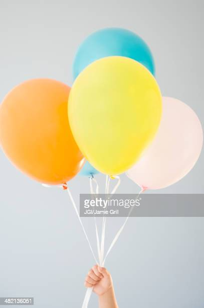 Korean girl holding bunch of balloons