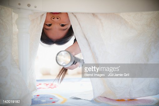Korean girl looking under bed with flashlight : Photo