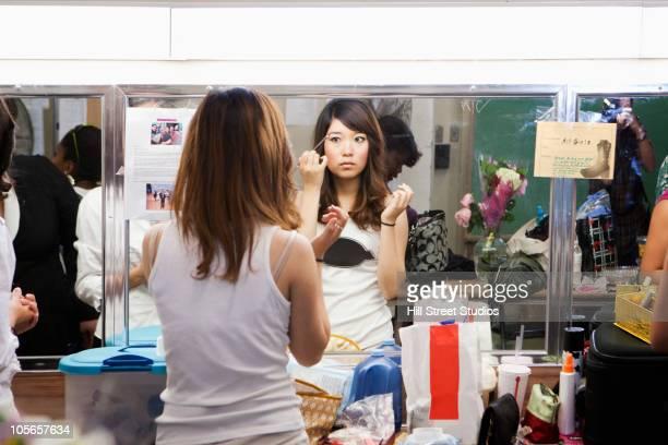 Korean girl putting makeup on backstage