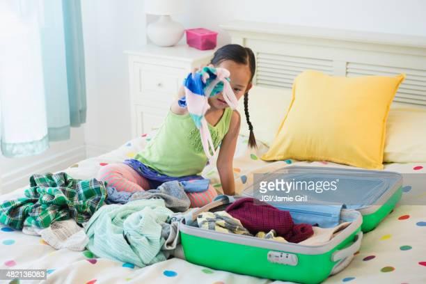 Korean girl unpacking suitcase on bed