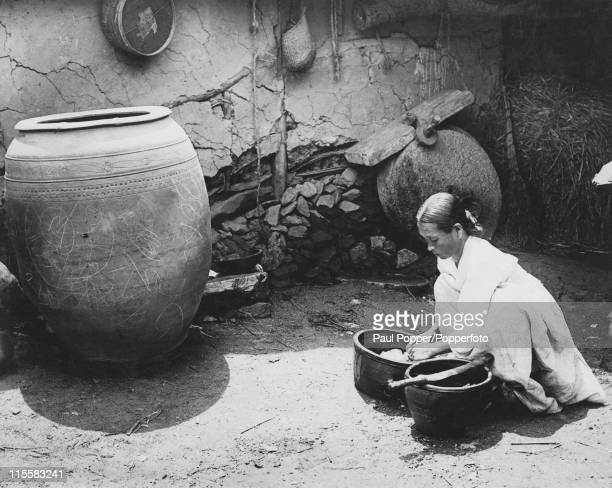 A Korean housewife washes clothes in two bowls circa 1920 The large jar stores the family's water supply