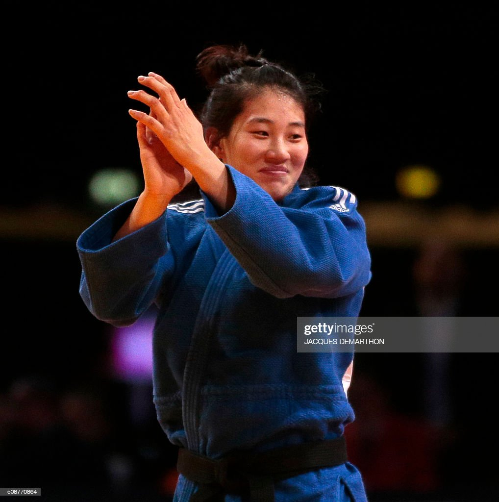 Korean Kim Jan-Di celebrates after winning against Mongolian Sumiya Dorjsuren in the women's under 57 kg final of the Paris Grand Slam Judo tournament on February 6, 2016 in Paris. / AFP / JACQUES DEMARTHON