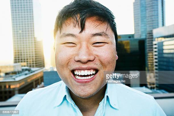 Korean man smiling on urban rooftop