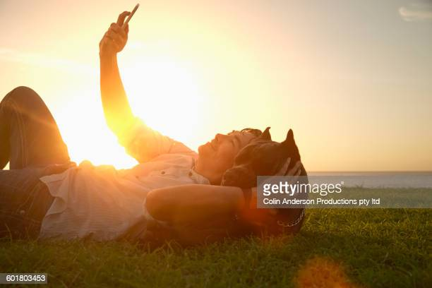 Korean man taking selfie with dog in field