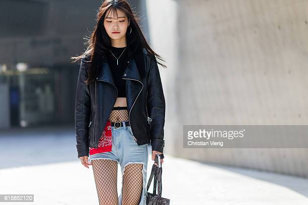 Korean model Jeong San ho wearing a black leather jacket cropped top red banda a ripped denim jeans net tights on October 20 2016 in Seoul South Korea