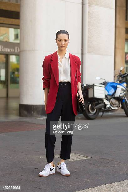Korean model Sung Hee Kim exits the Salvatore Ferragamo show at Piazza Affari in Nike sneakers on Day 5 of Milan Fashion Week Spring/Summer 2015 on...