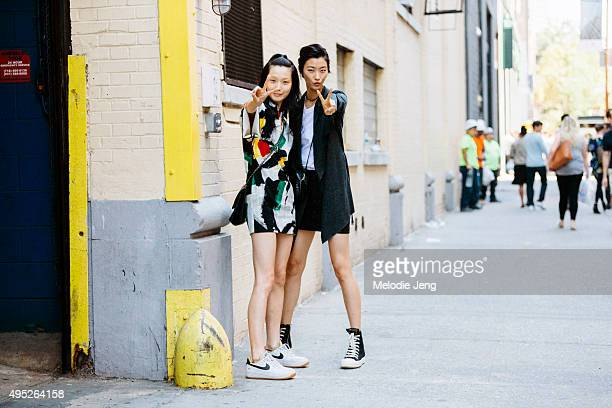Korean models Sunghee Kim and JiHye Park exit the J Mendel show on September 17 2015 in New York City Sunghee wears a paintpatterned color white...