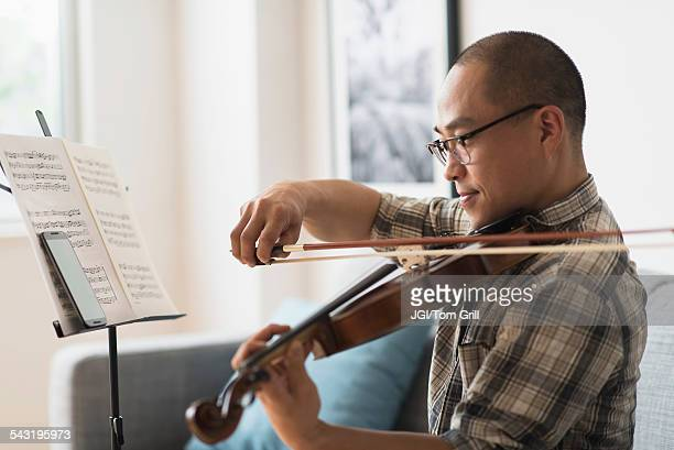 Korean musician playing violin in living room