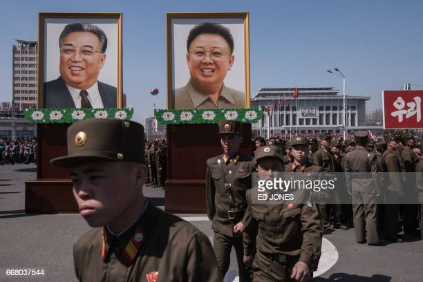 Korean People's Army soldiers walk before the portraits of late North Korean leaders Kim IlSung and Kim JongIl following the opening ceremony for the...