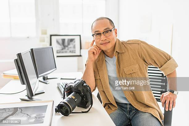 Korean photographer smiling at desk