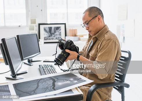Korean photographer using camera at desk