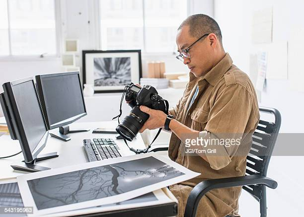 Korean photographer using camera at desk