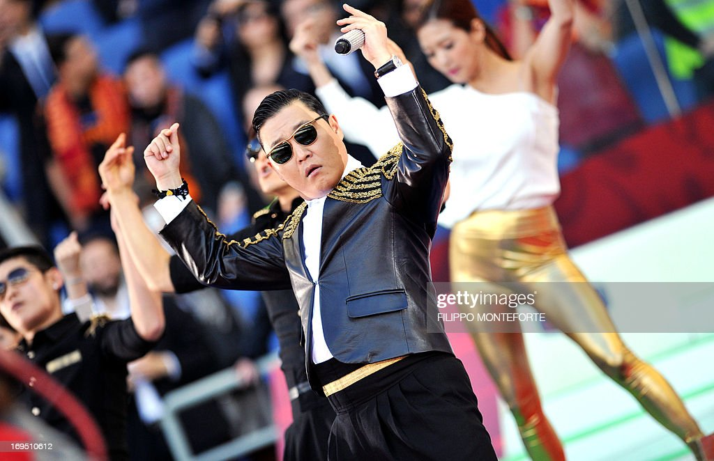 Korean pop artist Park Jae Sang (C), popularly known as 'Psy', sings as he performs his 'Gangnam Style' song prior to the Italian Cup football final between AS Roma and Lazio at the Rome's Olympic stadium on May 26, 2013.