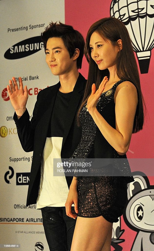 Korean pop groups Seohyun (R) of Girls' Generation and Suho (L) of EXO pose for photographers during a press conference in Singapore on November 23, 2012. The 8 mega-popular K-pop group are in Singapore for the SMTOWN Live World Tour III concert on November 23. .AFP PHOTO/ROSLAN RAHMAN