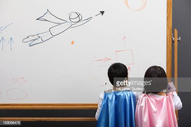 Korean superhero brother and sister writing on whiteboard