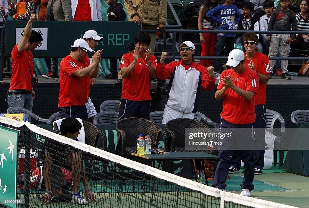 Korean team celebrates as Jeong Suk Young wins Davis cup reverse single match against VM Ranjeeth of India at Delhi Lawn Tennis Association stadium on February 3, 2013 in New Delhi, India.