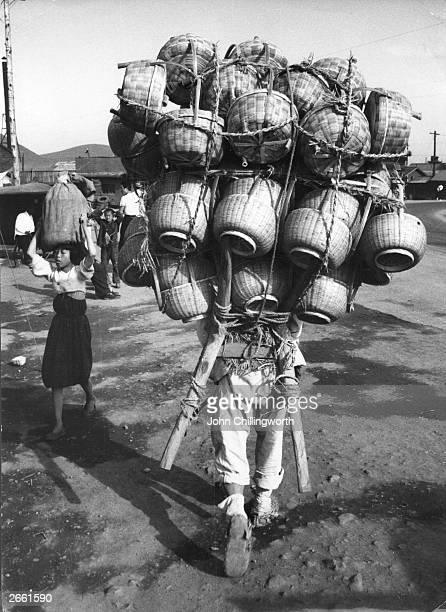 A Korean trader loaded with baskets in Pusan Original Publication Picture Post 7849 Korea I This is Your Country pub 1955
