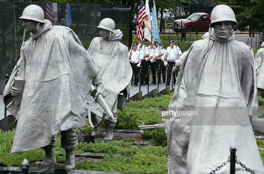 Korean War Veterans Color Guards march on the ground of the Korean War Veterans Memorial during a ceremony at the Korean War Veterans Memorial July...