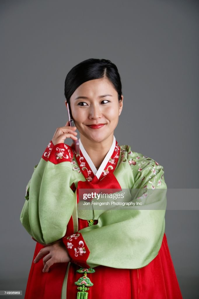 Korean woman in traditional dress talking on cell phone