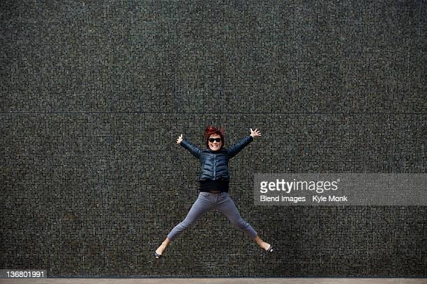 Korean woman jumping on city sidewalk