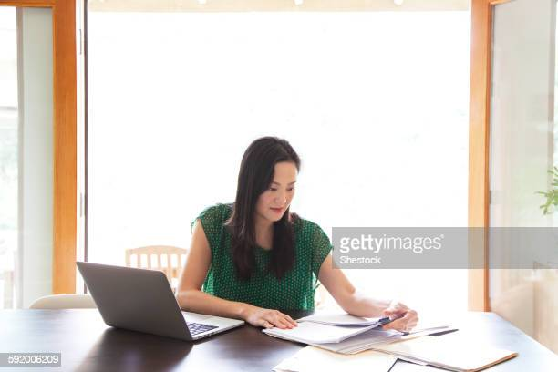 Korean woman paying bills on laptop