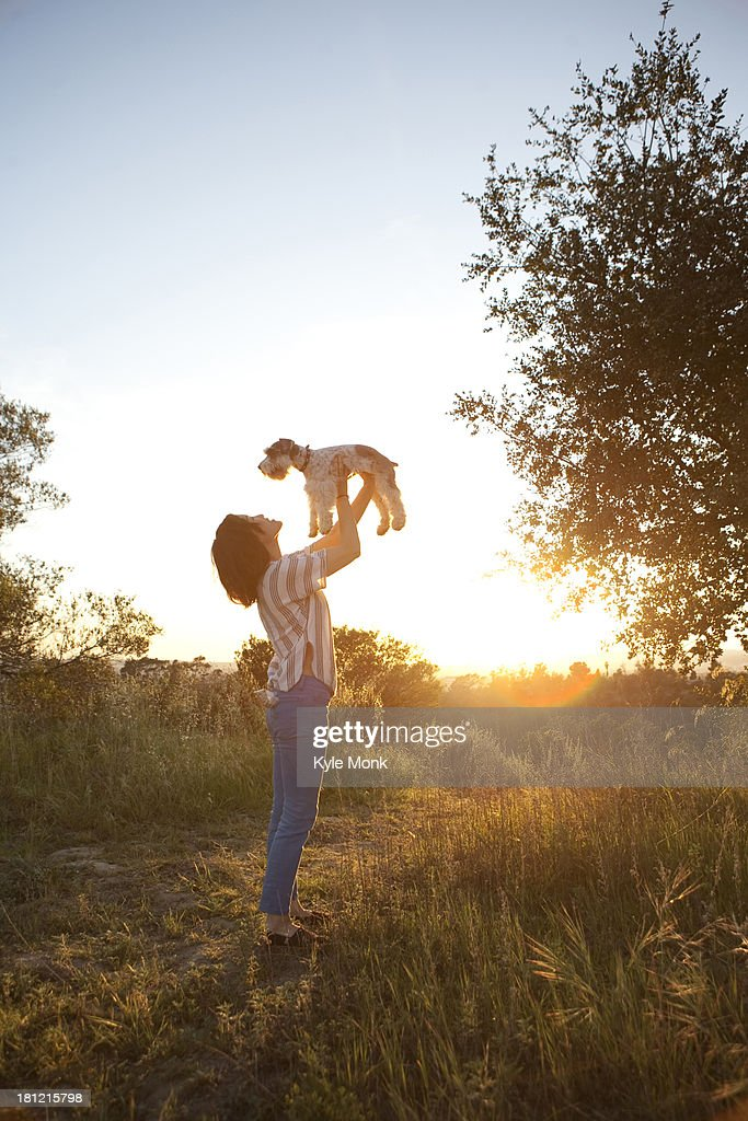 Korean woman playing with dog in meadow : Stock Photo