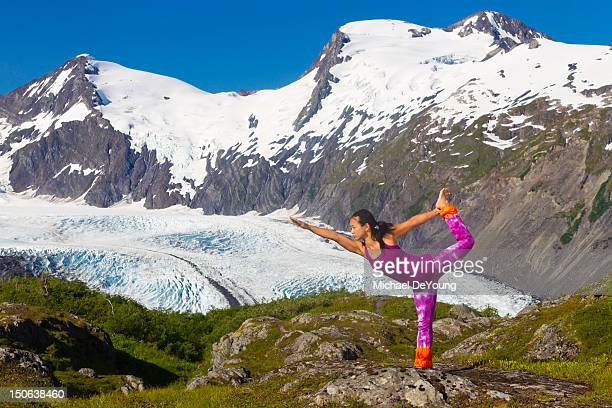 Korean woman practicing yoga with mountain in background