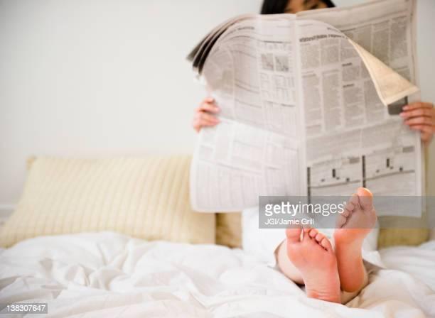 Korean woman reading newspaper in bed