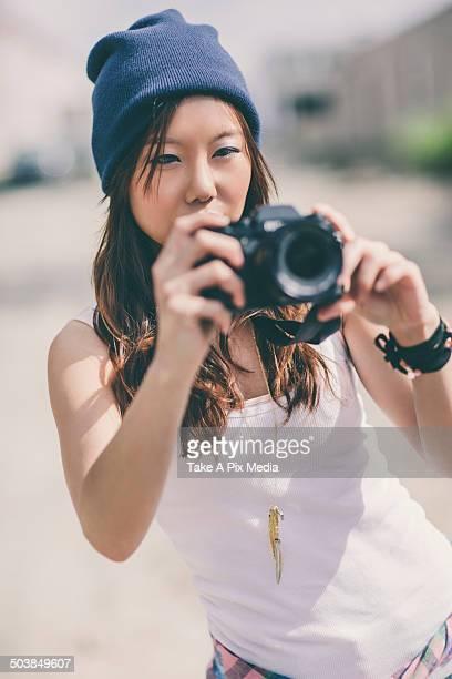 Korean woman taking pictures on city street