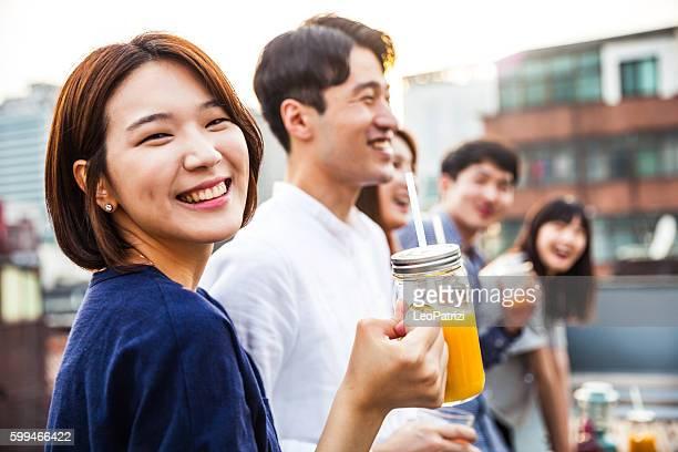 Donna coreana appoggiata sul tetto con amici, durante un party un seul