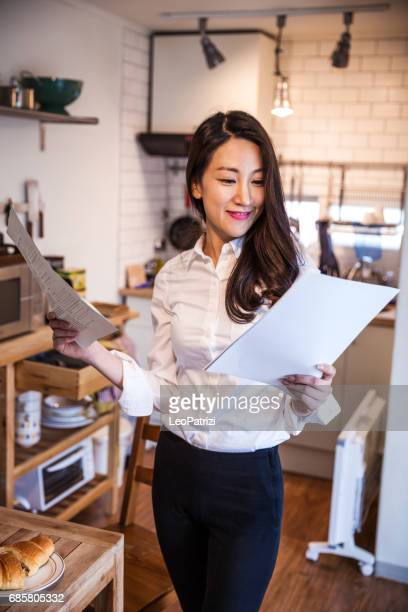 Korean woman working at home on contracts and mails