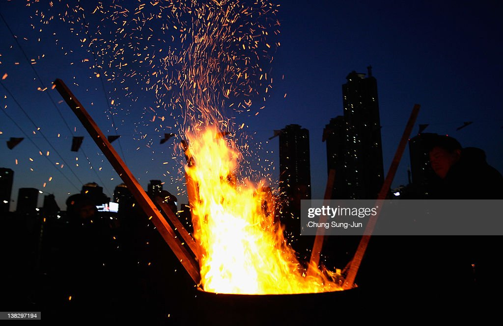 Koreans gather around a bonfire during 'Jwibulnoli' a South Korean folk game at Han River on February 5, 2012 in Seoul, South Korea. The event is part of a 'Daeboreum', a Korean holiday that celebrates the first full moon of the lunar new year.