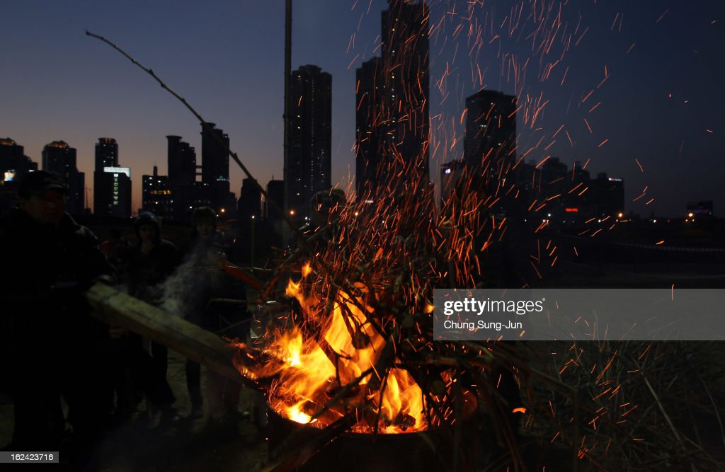 Koreans gather around a bonfire during 'Jwibulnoli' a South Korean folk game at Han River on February 23, 2012 in Seoul, South Korea. The event is part of a 'Daeboreum', a Korean holiday that celebrates the first full moon of the lunar new year.