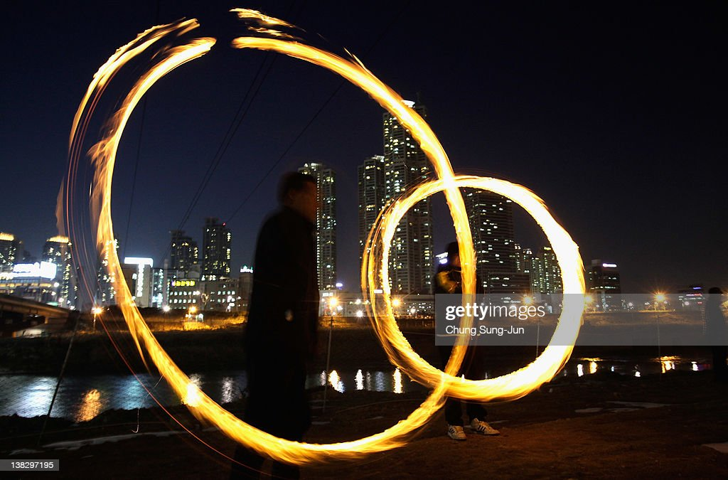 Koreans spin fire cans during 'Jwibulnoli' a South Korean folk game at Han River on February 5, 2012 in Seoul, South Korea. The event is part of a 'Daeboreum', a Korean holiday that celebrates the first full moon of the lunar new year.