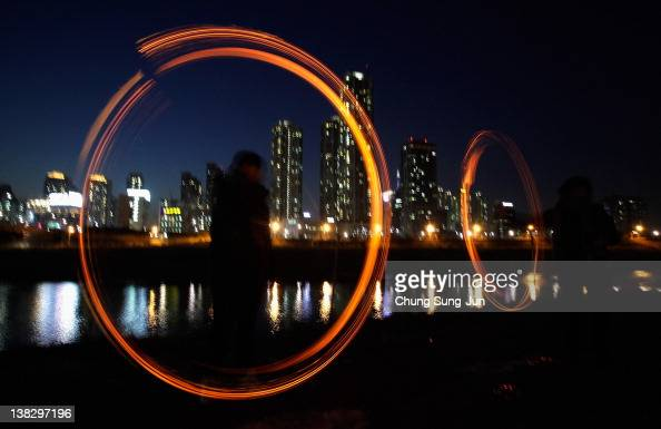 Koreans spin fire cans during 'Jwibulnoli' a South Korean folk game at Han River on February 5 2012 in Seoul South Korea The event is part of a...