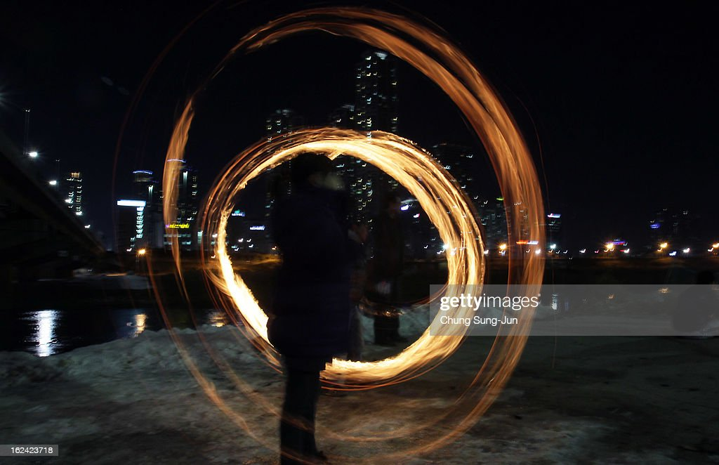 Koreans spin fire cans during 'Jwibulnoli' a South Korean folk game at Han River on February 23, 2012 in Seoul, South Korea. The event is part of a 'Daeboreum', a Korean holiday that celebrates the first full moon of the lunar new year.