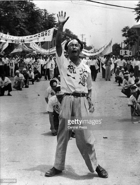 Koreans with slogans painted on their shirts including the phrases 'Advance to the North' and 'Unification' demonstrating in the streets on the...