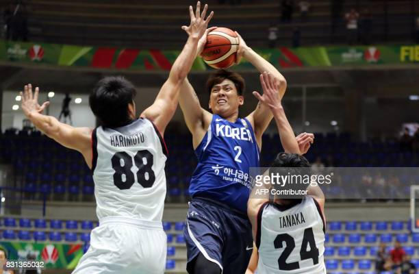 Korea's guard Choi Jungyong attempts to score as he is marked by Japan's forward Harimoto Tenketsu and guard Tanaka Daiki during their 2017 FIBA Asia...